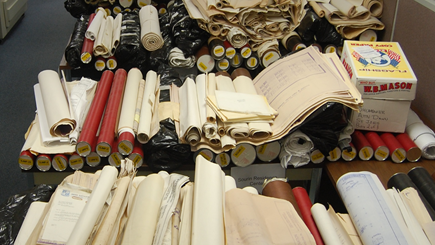 various cad documents rolled up and stacked